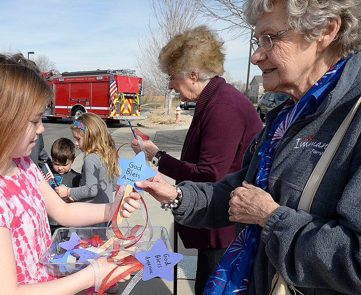 "Immanuel Lutheran School fourth-grader Natalie Siecgrist, 10, gives a hand-made ""flag-thingy"" to Shirley Goltz before lining the street to honor U.S. Marine Riley Schultz as a hearse carrying his body arrives at Immanuel Lutheran Church on Thursday, March 28, 2019, in Loveland. Fourth-graders at the school made about 100 of the patriotic decorations to hand out to people.  (Photo by Jenny Sparks/Loveland Reporter-Herald)"
