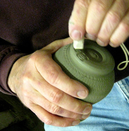 "Gary presses his ""seal"" into the soft clay."