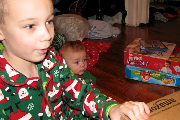 Koben opening a present while Nolan looks on