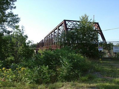 The rusted fencing suggests that the bridge was converted to pedestrian use for a while after the replacement bridge was built.