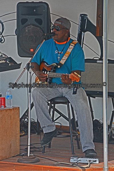 A local musician provides the cruise goers with some reggae tinged musical sounds on a lazy relaxing afternoon on the beach on Grand Turk.