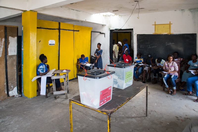 Monrovia, Liberia October 10, 2017 -  A poll worker checks a voter's ID card at a polling station as election observers watch.