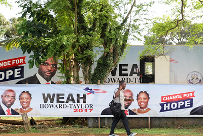 Monrovia Liberia October 5, 2017 - A man walks past political signs prior to the 2017 presidential election.