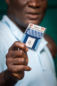 Monrovia, Liberia October 10, 2017 -  A voter shows his voter ID card while standing in line on election day.