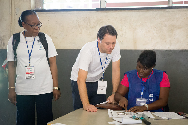Monrovia, Liberia October 10, 2017 -  Jason Carter and Madame Samba-Panza speak with a polling worker on election day.