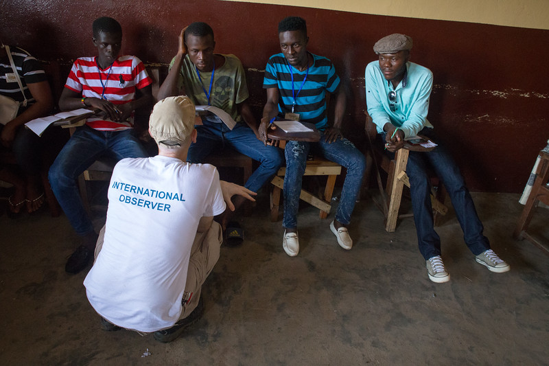 Monrovia, Liberia October 10, 2017 - Nick Jahr checks in elction day activity by talking with local election observers.