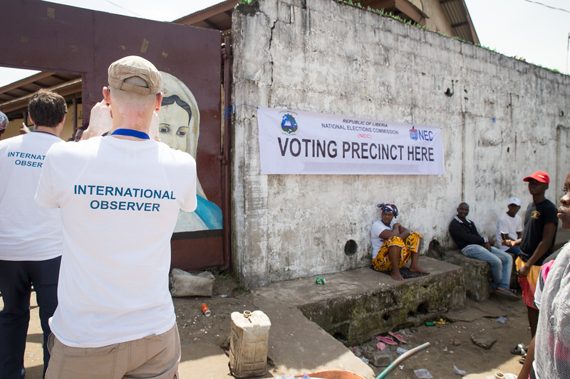 Monrovia, Liberia October 10, 2017 -  Jason Carter and Nick Jahr check in on voting activity at a polling station on election day.