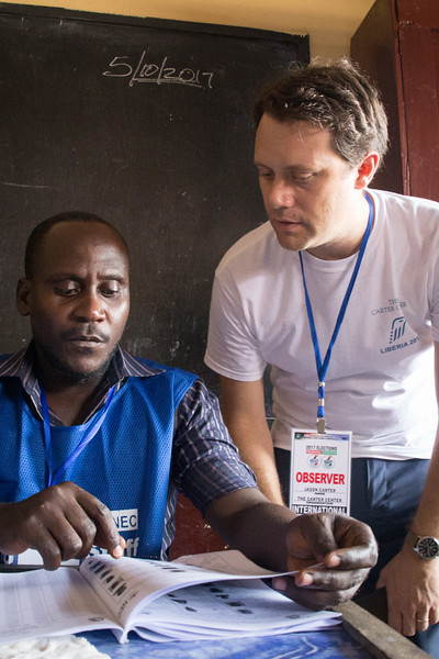 Monrovia, Liberia October 10, 2017 - Jason Carter talks with a poll worker on election day.