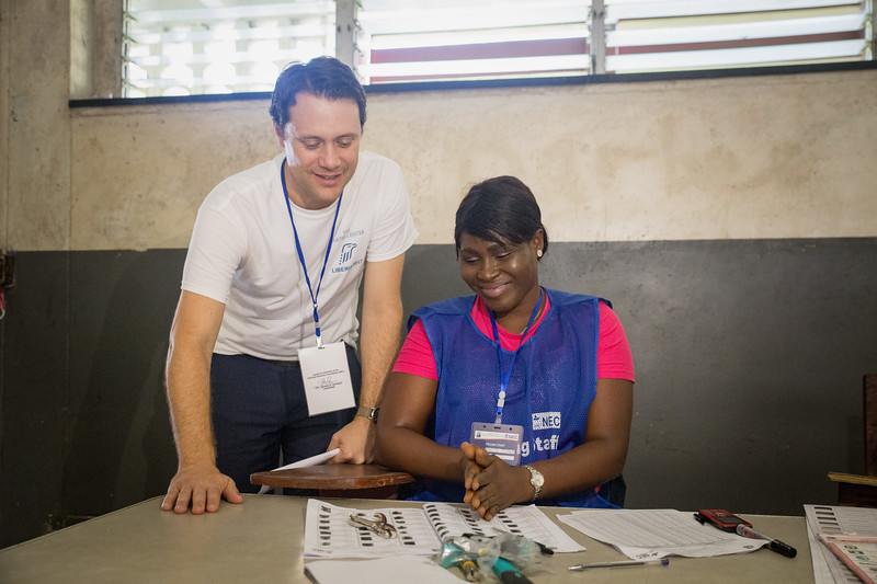 Monrovia, Liberia October 10, 2017 -  Jason Carter speaks with a poll worker on election day.