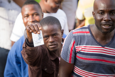 Monrovia, Liberia October 10, 2017 -  A voter stand in line on election day displays his voter ID card.