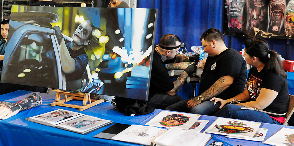 . (Chris Riley/Times-Herald) Nicholas Sorci, of Vallejo, is comforted by Ashley Walden as he gets tattoed by Richard Reynolds from Delta Art and Tattoo Collective during The Catalyst Tattoo Expo at the Solano County Fairgrounds in Vallejo on Friday.