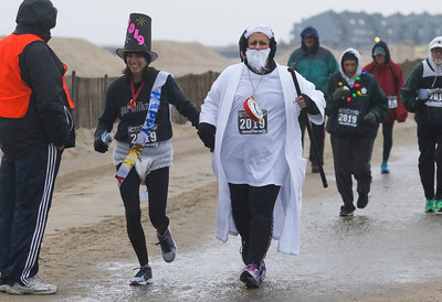 [On left] Laurie Moore, from Avon, as baby new year and Kim Calafiore, from Avon, as father time. The 2018 Twilight Run in Manasquan, NJ on 12/21/18. [DANIELLA HEMINGHAUS | THE COAST STAR]