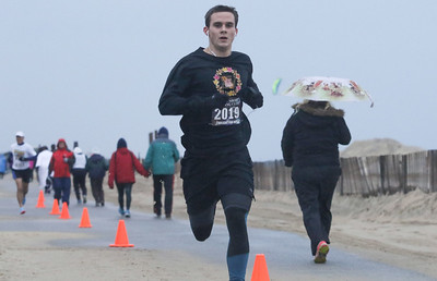 1rst place overall runner, Connor Lewis, from Glen Ridge, crossing the finish line. The 2018 Twilight Run in Manasquan, NJ on 12/21/18. [DANIELLA HEMINGHAUS | THE COAST STAR]