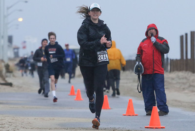 Emily Zeigler, from Manasquan, running in as the first female finisher. The 2018 Twilight Run in Manasquan, NJ on 12/21/18. [DANIELLA HEMINGHAUS | THE COAST STAR]