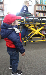 "Ethan Hodes, from Sea Girt, watches Karen Crawley set up. Manasquan First Aid Squad visiting Sea Girt library to teach the children about what they do as a part of the library's ""People In Our Neighborhood"" series. [DANIELLA HEMINGHAUS 