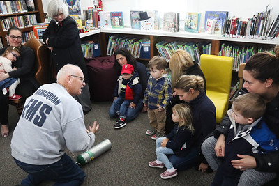 "John O'Grady teaching kids and parent about an oxygen tank. Manasquan First Aid Squad visiting Sea Girt library to teach the children about what they do as a part of the library's ""People In Our Neighborhood"" series. [DANIELLA HEMINGHAUS 