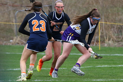 St. Rose High School takes on Trinity Hall High School in a girls varsity lacrosse game held on Tuesday April 17, 2018. Kara Reilly (right) from St. Rose scoops up the ball around Trinity Hall defenders during game action. (MARK R. SULLIVAN /THE COAST STAR)