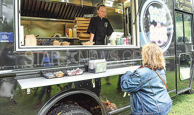 emily hodecker, co-owner of the good mood good food truck taking an order at the festival.