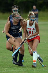 #21, Claire Ferguson of the Wall High School Girl's Varsity Field Hockey Team works the ball past #50, Meghan Catlani of Manasquan High School during their game played in Wall, NJ on 09/05/2019. (STEVE WEXLER/THE COAST STAR).
