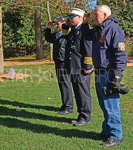 l-r: keith de laura. former slh fire chief. councilman and firefighter joe tempey. and bill fury  slh  firefighter. saluting the flag.