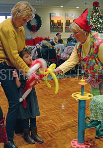 linda nitch and her granddaughter leah galok.msq. getting a bloon candycane from nancy divito[dressed as an elf clown].