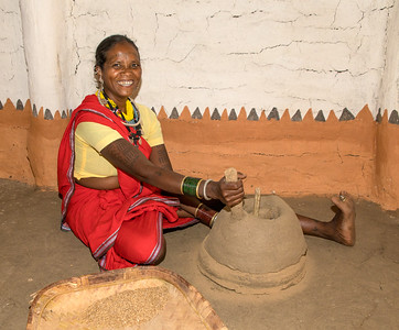 """A lady of the Baiga tribe around Kanha demonstrating the traditional way of grinding wheat. While milling is no longer done this way, TCF enthusiastically supports a museum of Baiga tribal culture where the """"old ways"""" are not forgotten. This helps build trust and cooperation with local people, who are essential partners in TCF's wildlife conservation mission."""