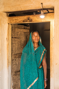 A lady of the Gond tribe in the Kanha-Pench Wildlife Corridor admiring the first electric light her family has ever had, powered by solar panel and battery. TCF offers small solar systems to families in order to build trust and improve their lives.
