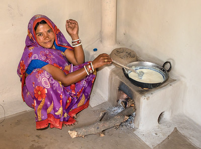 A farm wife cooking on an improved-design chula stove pioneered by TCF. Traditional chula stoves have no chimney and are very inefficient, requiring more wood from the forest. The new stove vents through a chimney, nearly eliminating interior smoke, a leading cause of COPD and other respiratory diseases common among rural populations, and saves a great deal of wood.