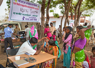Dr. Umesh Kumar Namdeo examining a young patient at a shadetree clinic in the village of Bakiguda  near Kanha as part of TCF's Rural Medical Outreach Programme.
