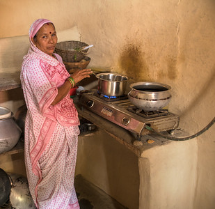 A farm lady cooking with biogas produced by an outside underground digester provided by TCF. The farmer feeds a slurry of cow dung and water into the concrete digester which provides a continuous source of biogas which enters the house through the hose on the right in the photo. This eliminates the need to gather wood from the forest for cooking.