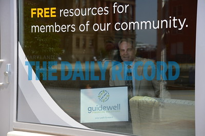6.1.16 BALTIMORE, MD-Matthew Gregory, Housing Councilor holding up the Guidewell sign in the window of the University of Maryland Community Engagement Center, where he give free home counseling services on Wednesdays.  (The Daily Record/Maximilian Franz)