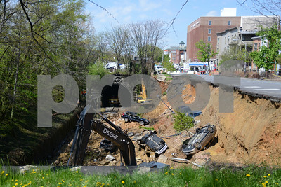 05.01.14- BALTIMORE, MD- Photo of earth movers working to clean up the dirt, cars and debris that fell into the CSX tracks along 26th Street between Charles and St. Paul Streets. (The Daily Record/Maximilian Franz),