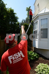 5.26.16 BALTIMORE, MD- Shawn Stachowiak, operations manager for Fish Window Cleaning, up on a ladder power washing a home near Annapolis, with Franchise owner Jim Brown overseeing from the ground.  (The Daily Record/Maximilian Franz)