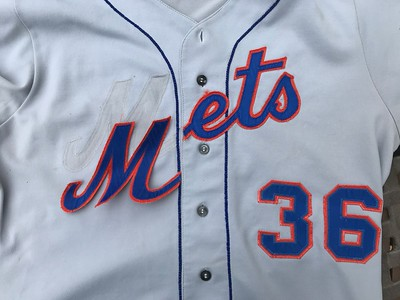 """Like most Mets jerseys of the era, once their MLB service was done, they were shipped to the minors for often many more years of daily use. But while the Mets' farm team  might use the parent club's name, displaying the MLB city name on the front of team jerseys wouldn't do.  Therefore, it was very common for the  original """"NEW YORK"""" to be stripped from the front and replaced with the home script. Here, I have begin the removal of the replacement lettering to begin the restoration."""
