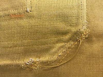 """If you look carefully at this spot at the right bottom corner of the removed """"3"""" we can see 1963-vintage darning machine fabric repair in gold thread. Look closely at the horizontal ghost line near the center of the photo. That is the line from the original bottom of the """"2"""" that had been there. There is no way I am going to make the new 2 that small just to match the line... this is just another clue of how much this fabric has shrunk since original. Common sense must prevail."""