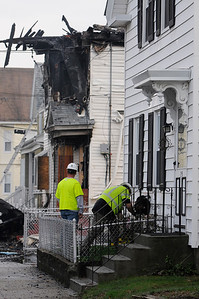 TIM JEAN/Staff photo  Gas workers check the meters on a house next to 23 Brookfield St., Lawrence while firefighters spray water on hot spots hours after getting the three-alarm fire under control. The building was vacant due to being heavily damaged in the Sept. 13 gas disaster.    4/19/19