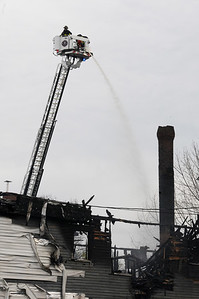 TIM JEAN/Staff photo  Firefighters spray water on hot spots hours after getting the three-alarm fire under control at 23 Brookfield Street in South Lawrence. The building was vacant due to being heavily damaged in the Sept. 13 gas disaster.    4/19/19