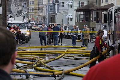 TIM JEAN/Staff photo  A group of residents watch as firefighters spray water on hot spots hours after getting the three-alarm fire under control at 23 Brookfield Street in South Lawrence. The building was vacant due to being heavily damaged in the Sept. 13 gas disaster.    4/19/19