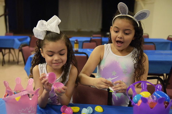 TIM JEAN/Staff photo  Jarielys Ramos, 5, left, of Haverhill, and her sister Ailanis, 6, look inside the eggs for treats after the Trinity Episcopal Church in Haverhill annual Easter Egg Hunt.  4/20/19