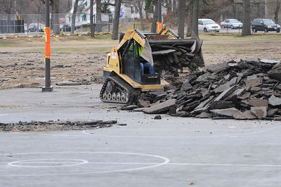 TIM JEAN/Staff photo  Heavy equipment removes the basketball and tennis courts near Veterans Memorial Stadium in Lawrence where travel trailers house displaced residents after the Sept. 13 gas explosions and fires. Columbia Gas said it would make any necessary repairs to the area that resulted from the use.     4/18/19
