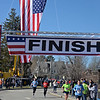 RYAN HUTTON/ Staff photo<br /> With a giant American flag flying above them, runners head toward the finish line of the Run for the Troops 5K at Whittier Court in Andover on Sunday.