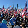 RYAN HUTTON/ Staff photo<br /> Cadets from the Norther Essex Community College/ Methuen Police Department police academy carry American flags high as they cool down after crossing the finish line of the Run for the Troops 5K at Whittier Court in Andover on Sunday.