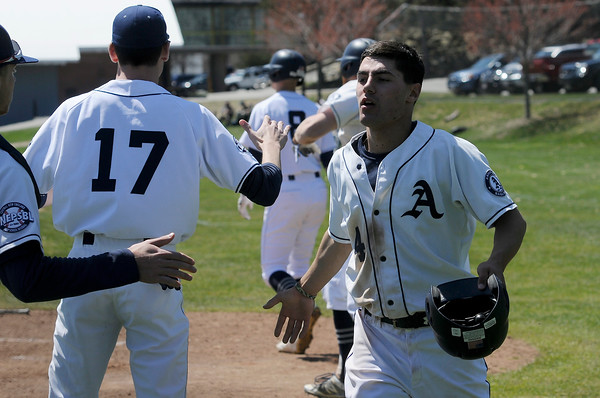 TIM JEAN/Staff photo<br />   <br /> At right, Phillips Academy's Joe Simourian, of Andover, high fives his teammates after scoring a run during a baseball game against Worcester Academy. 4/21/18