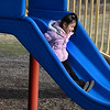 CARL RUSSO/Staff photo Loyda Say, 6 of Haverhill  plays on the slide at Winnekenni Park on March 18. <br /> <br /> Haverhill people took advantage of a sunny and mild Wednesday afternoon to enjoy the day and forget about the coronavirus, for at least a little while<br /> <br /> With temperatures in the 50's, neighbors  walked the Winnekenni Park trail and played in the park. Across town others stopped to buy ice cream at Carter's Ice Cream stand in Bradford. 3/18/2020