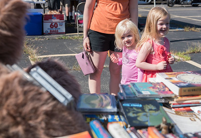 AMANDA SABGA/Staff photo  sisters Julia, 3, and Abigail Mead, 4, of Derryook at items for sale during the 41st Annual Derry Rotary Club Auction at the Fireye parking lot in Derry.   8/24/19
