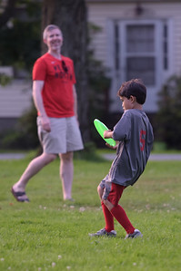 TIM JEAN/Staff photo  Andrew Smith, left, of Andover, plays a game of frisbee with his son Caleb, 7, as they listen to the Katrina Marie Band during Andover's Concerts in the Park series.   8/22/19