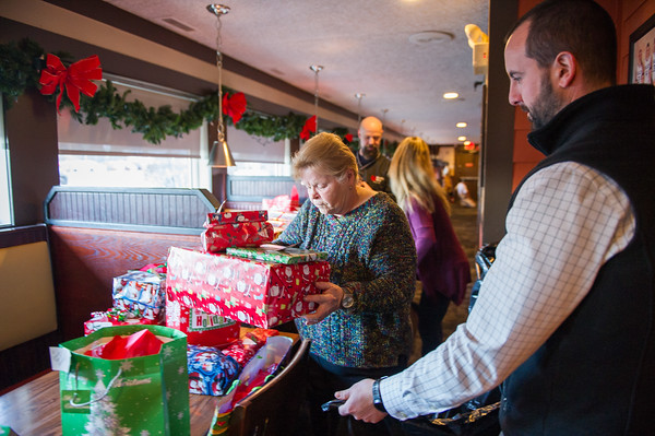 AMANDA SABGA/Staff photo   Diane Mackey and Pj Boncek, 99 Restaurants Regional Operations Director, pack gifts at the Ninety Nine Restaurant in Salem that will be taken to families in need.    12/18/18