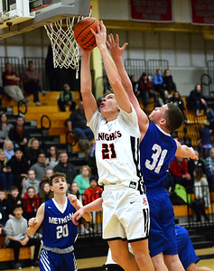 CARL RUSSO/Staff photo North Andover's Brett Dunham fights to make the lay up as Methuen's Andrew Lussier defends under the hoop. The North Andover Knights defeated the Methuen Rangers 69-39 in boys basketball action. 12/14/2018