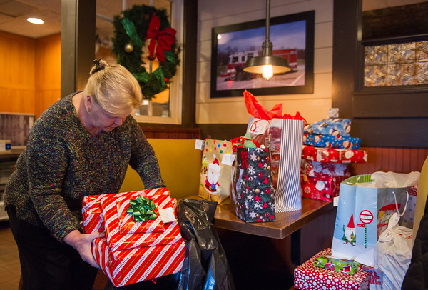 AMANDA SABGA/Staff photo   Diane Mackey packs gifts at the Ninety Nine Restaurant in Salem that will be taken to families in need.      12/18/18