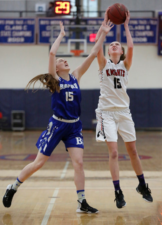 MIKE SPRINGER/Staff photo North Andover's Katherine Robie, right, goes up for a shot under defensive pressure from Julia Dearing of Bedford at Tewksbury Memorial High School. 12/16/2018